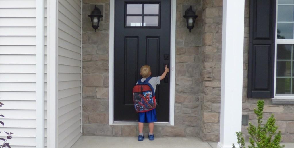 boy with Spiderman backpack opening black door