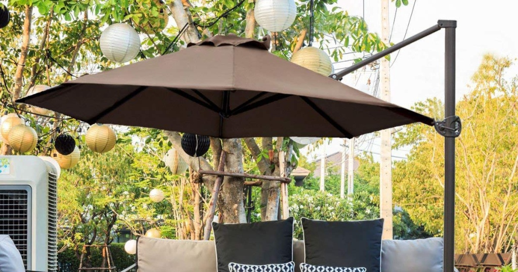 Cocoa Abba Patio offset 11 foot outdoor umbrella with outdoor couches and lanterns