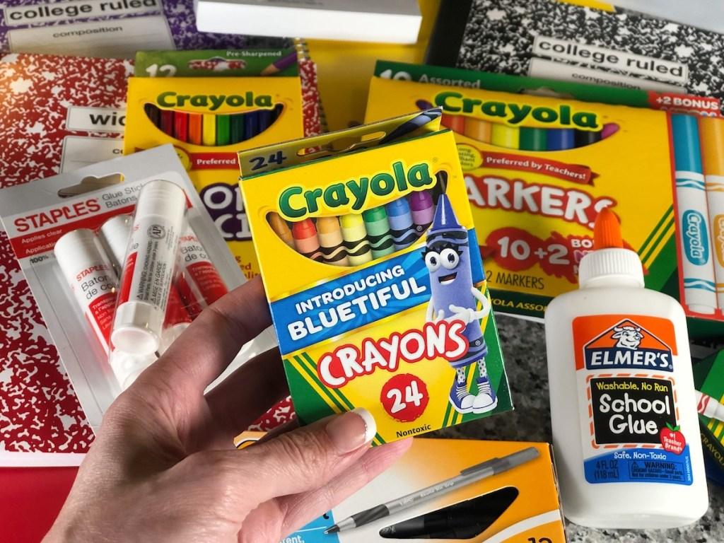 crayola crayons held up above school supplies