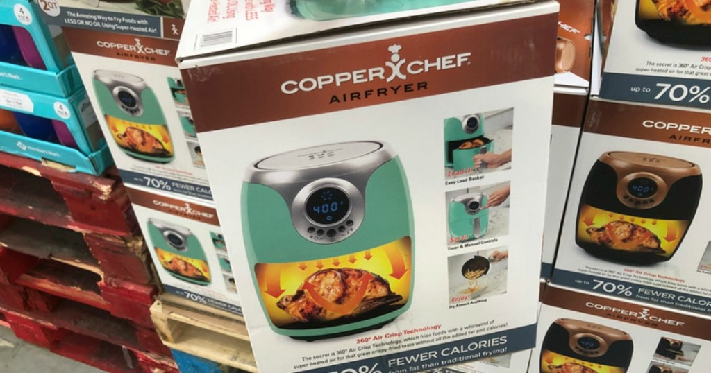 copper chef teal air fryer being held in front of other air fryers
