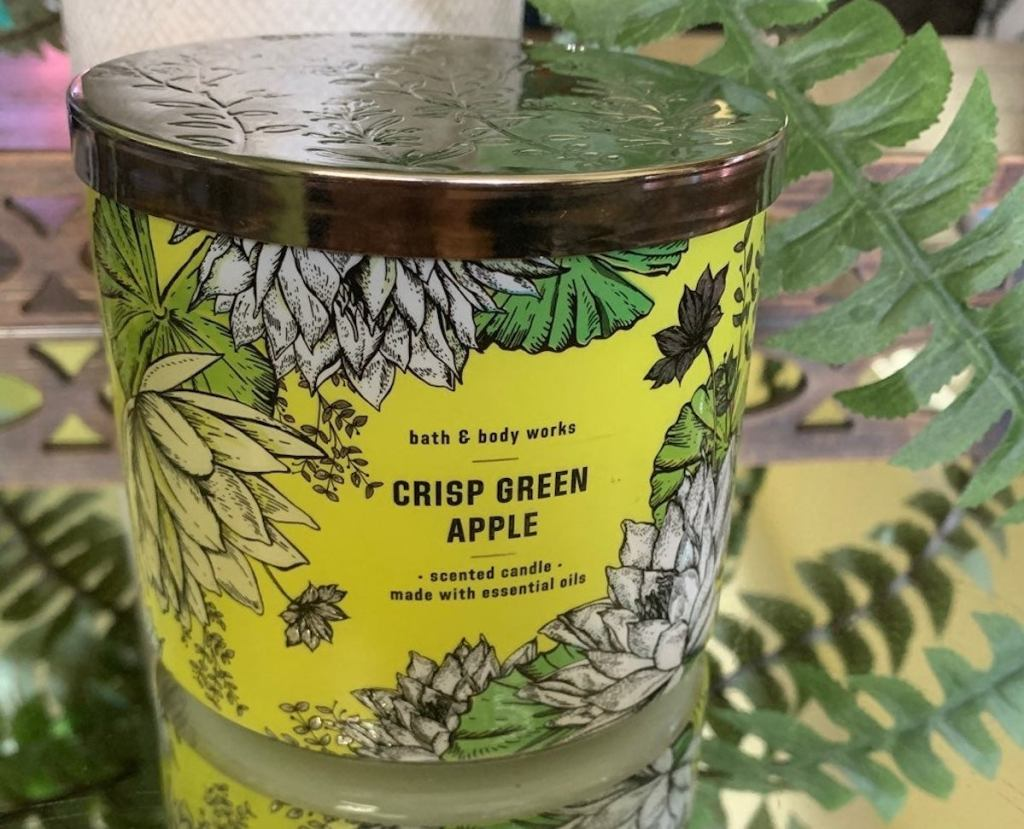crisp green apple candle sitting on mirrored table