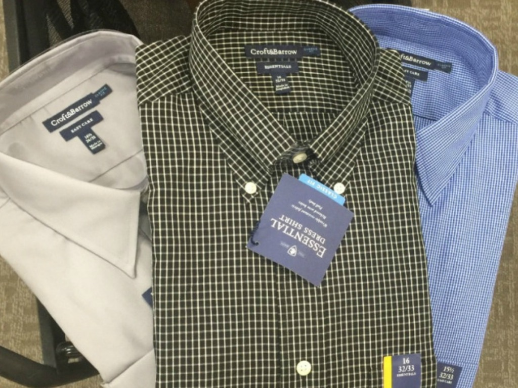 three men's dress shirts on a cart in a store