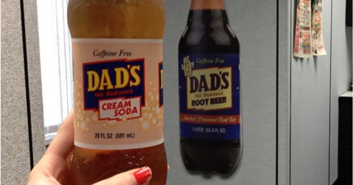 hand holding dad's cream soda in front of dad's root beer sign hanging on cubicle
