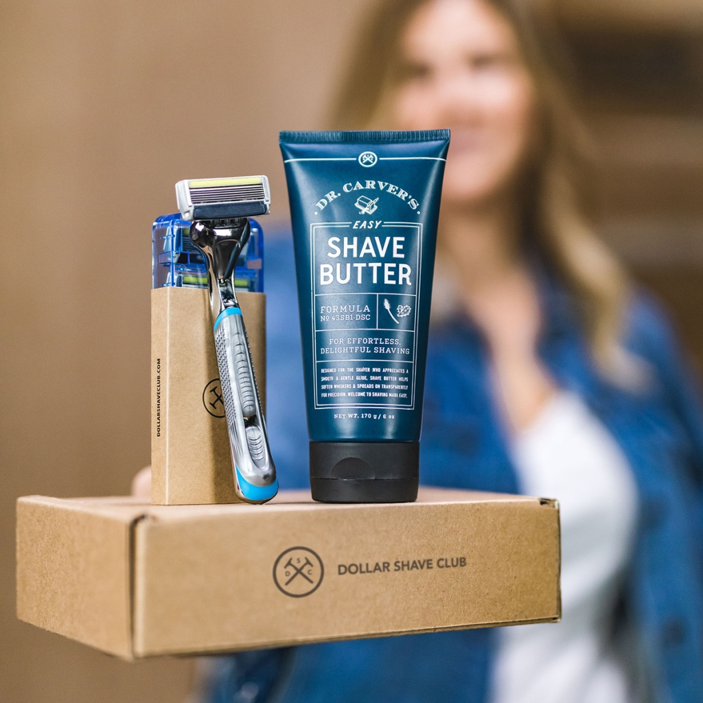 woman holding up dollar shave club box