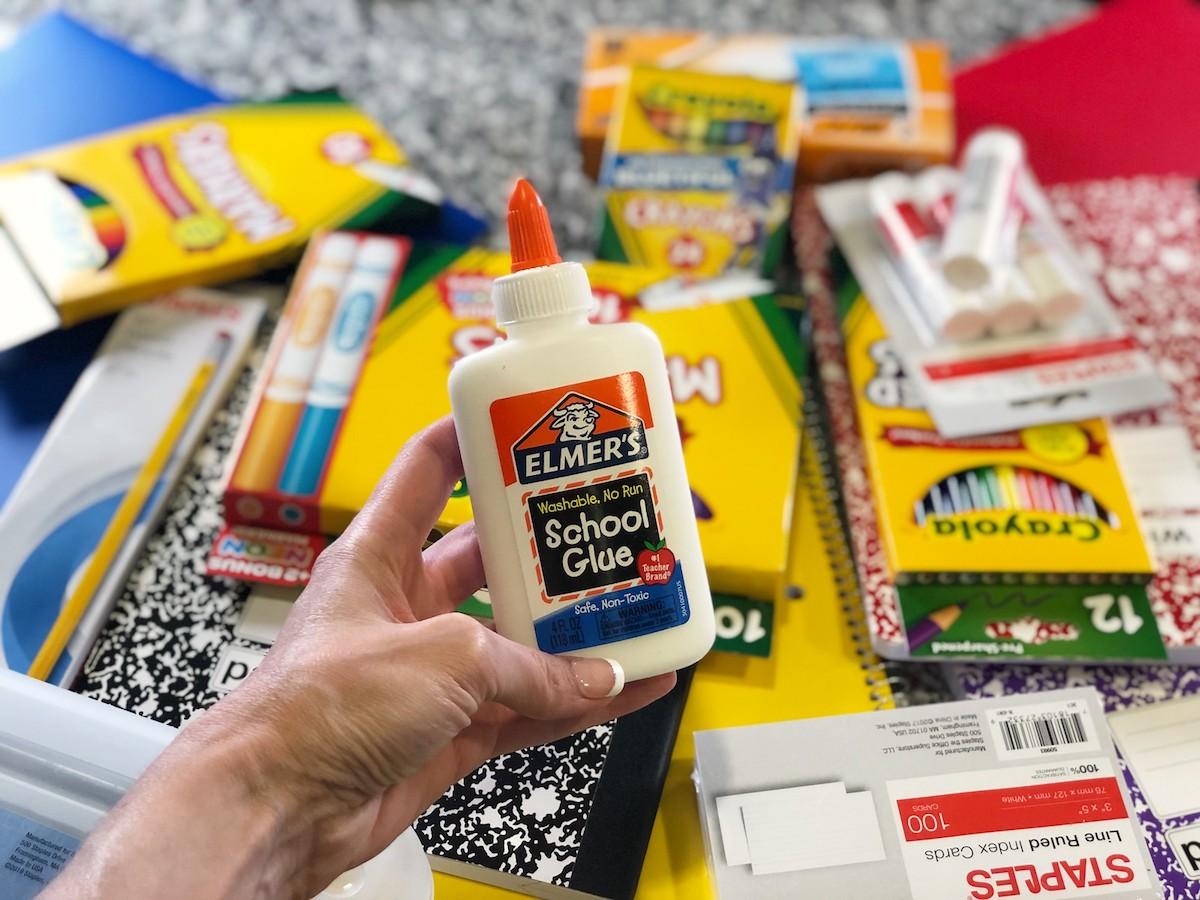 Elmer's Glue held above pile of school supplies