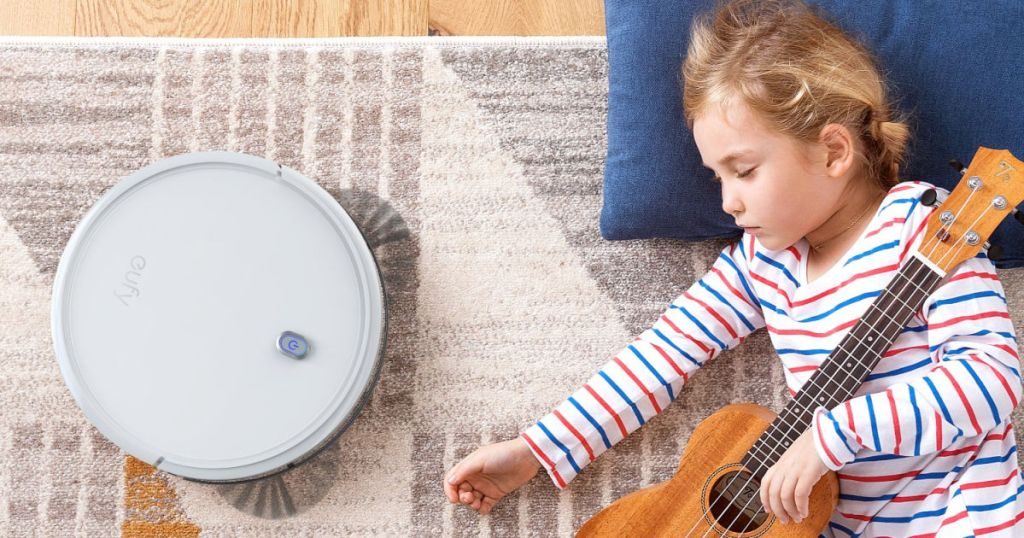 child sleeping holding a guitar on the floor next to operating eufy BoostIQ RoboVac 11S Robot Vacuum