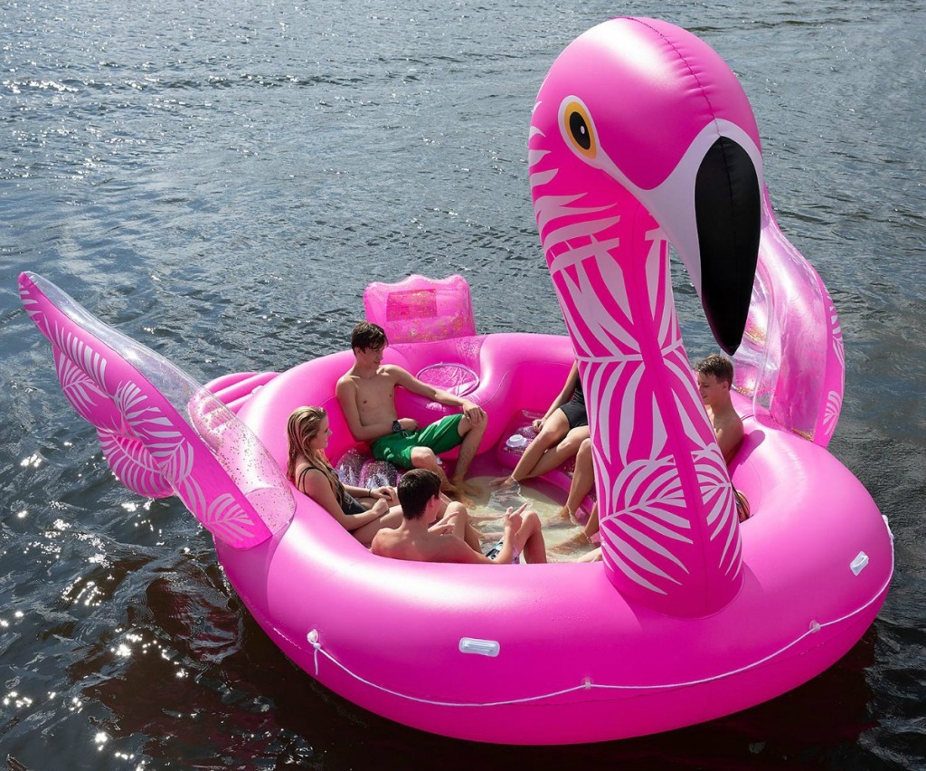 huge inflatable flamingo party float on the ocean with people lounging