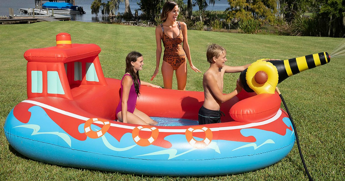 kids playing in fire boat portable pool with woman watching