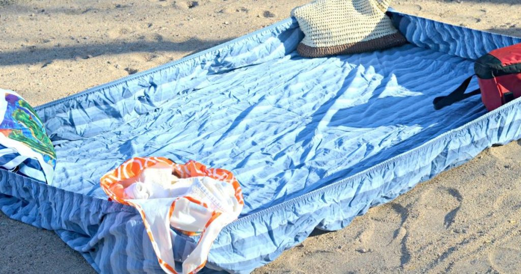 blue fitted sheet on sand with stuff in each corner