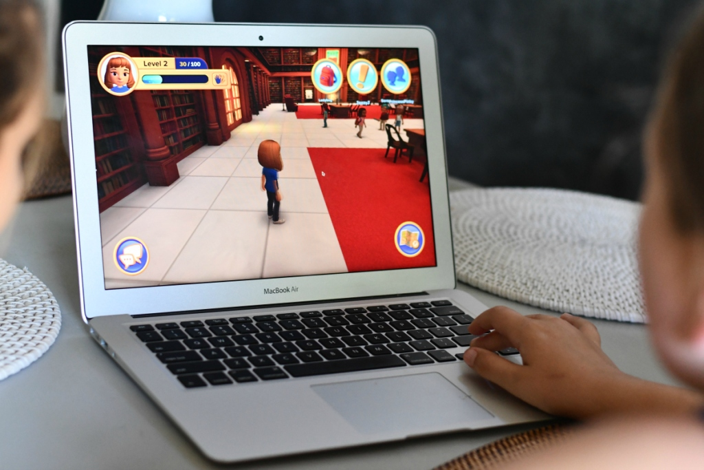girl playing Adventure Academy on MacBook Air