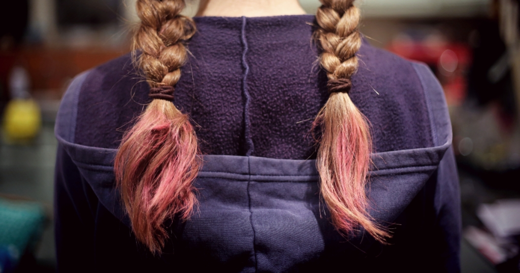 back of girl's head with braided hair in a navy hoodie