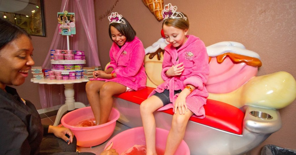 two girls in pink robes having pedicures