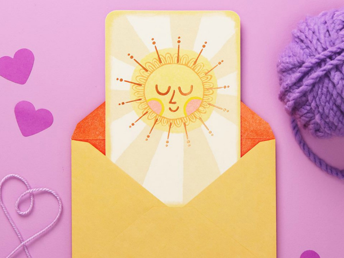 Sunshine themed greeting card in a yellow envelope on a purple surface