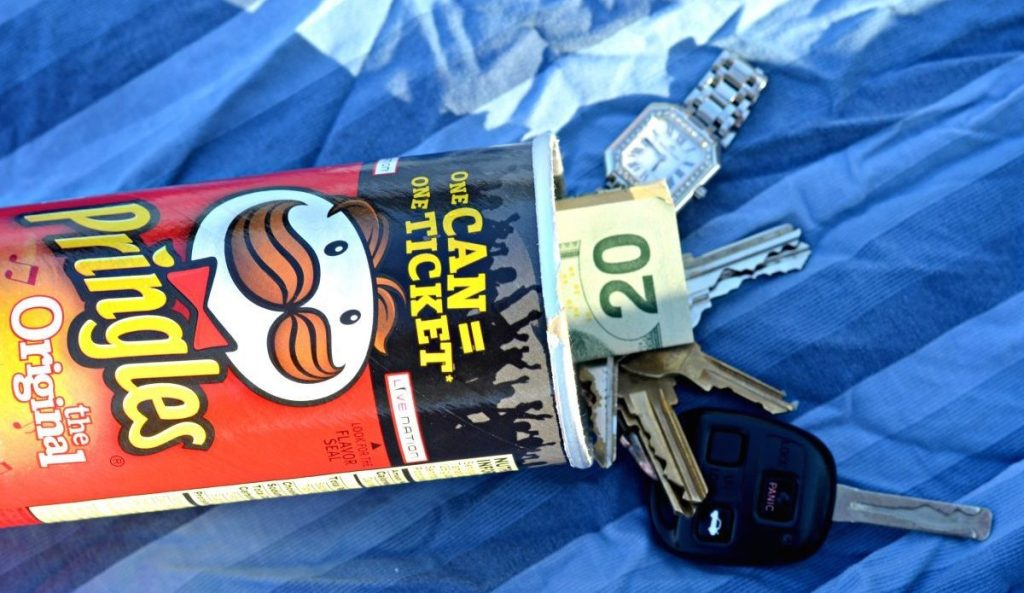 pringles container with money keys and watch inside