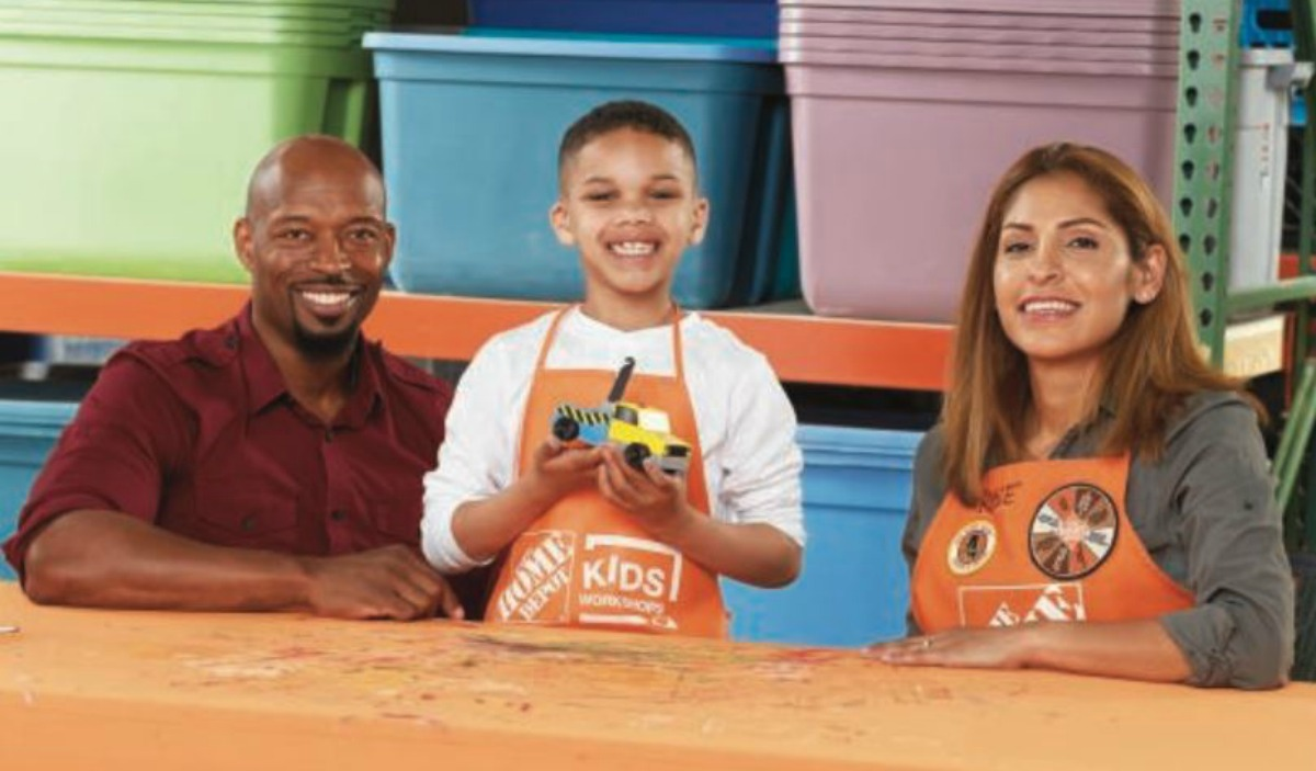 man smiling, boy holding wooden tow truck, and woman wearing home depot apron