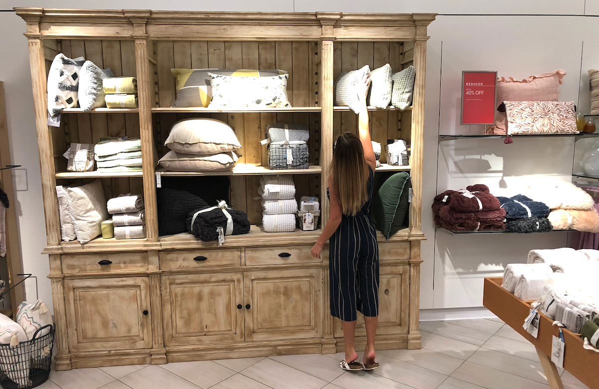 woman reaching to top of cabinets with pillows shopping the nordstrom anniversary sale