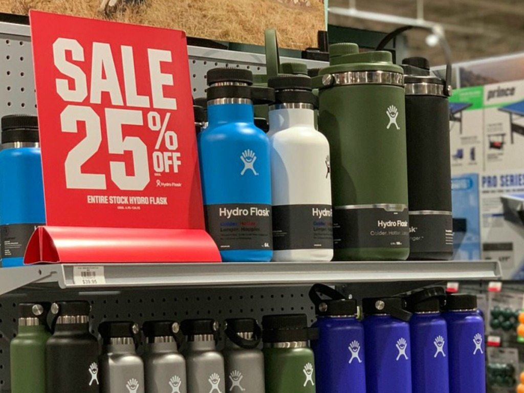 water bottles in different size on store shelf by red sign