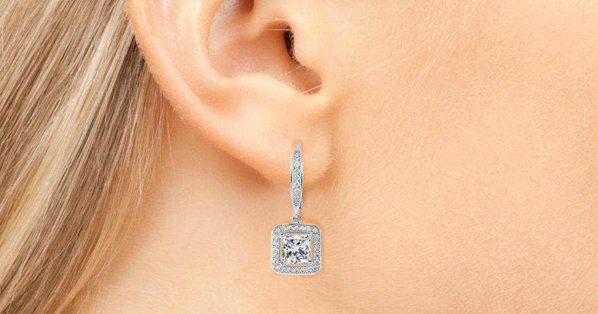 closeup of diamond square drop earrings on a woman's ear
