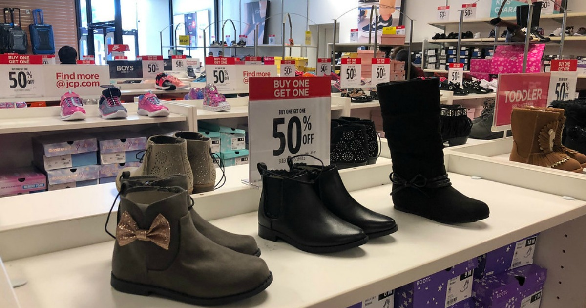 shoes and boots on shelves with sale signs inside