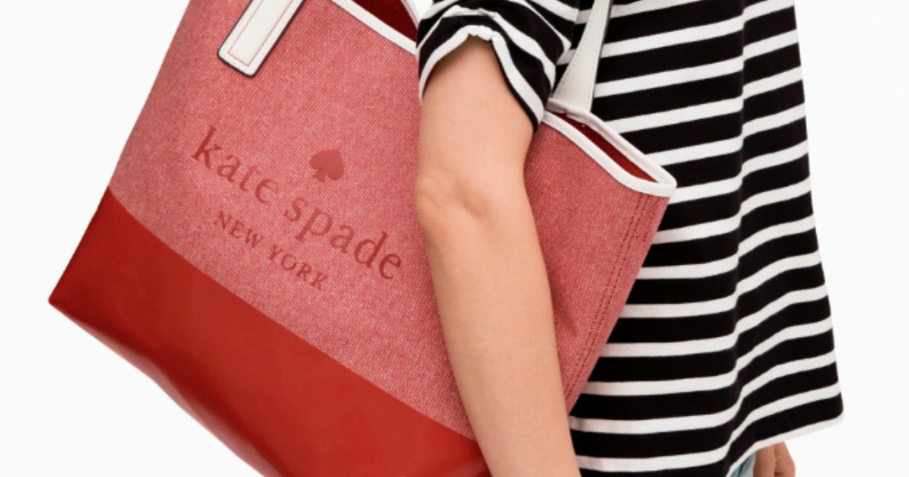 woman in blue and white shirt carrying kate spade red handbag
