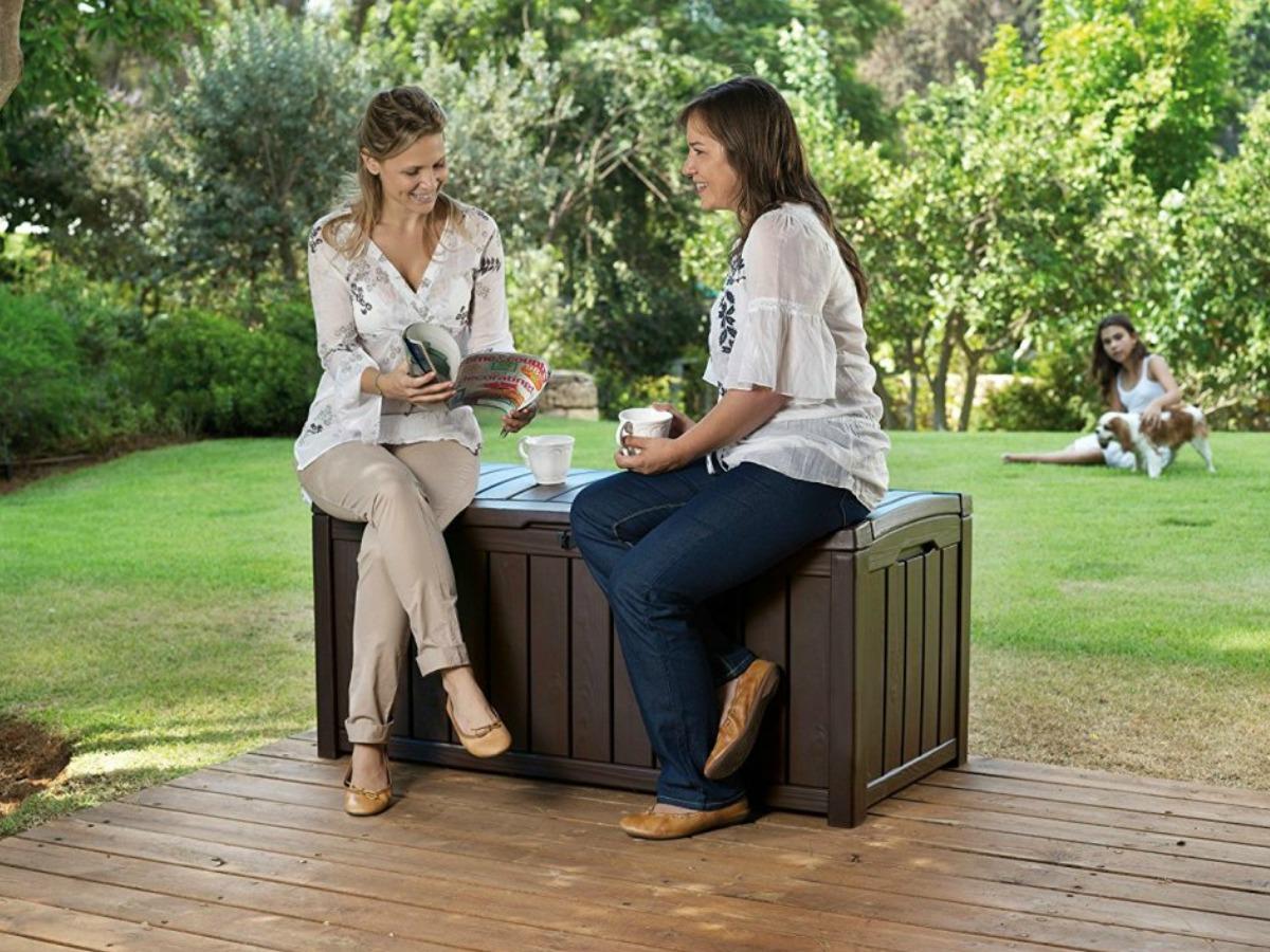 two women sitting on a deck box talking
