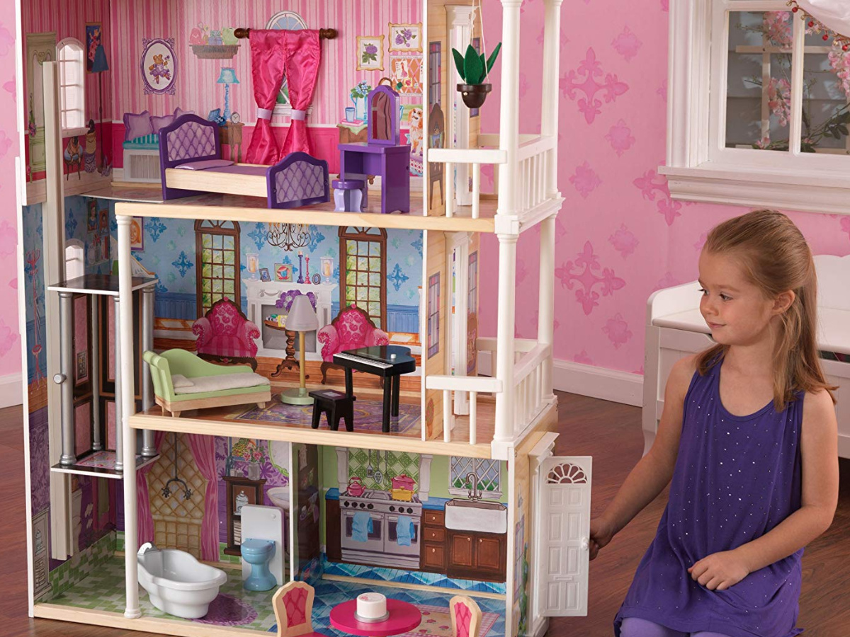 little girl in purple dress playing with large dollhouse