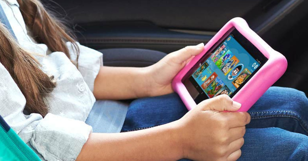 girl seated in car holding on her lap a fire tablet with pink case