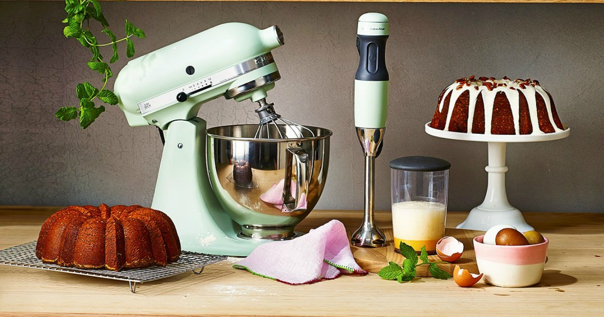 light green Kitchenaid mixer on wooden counter next to immersion blender and several baked goods