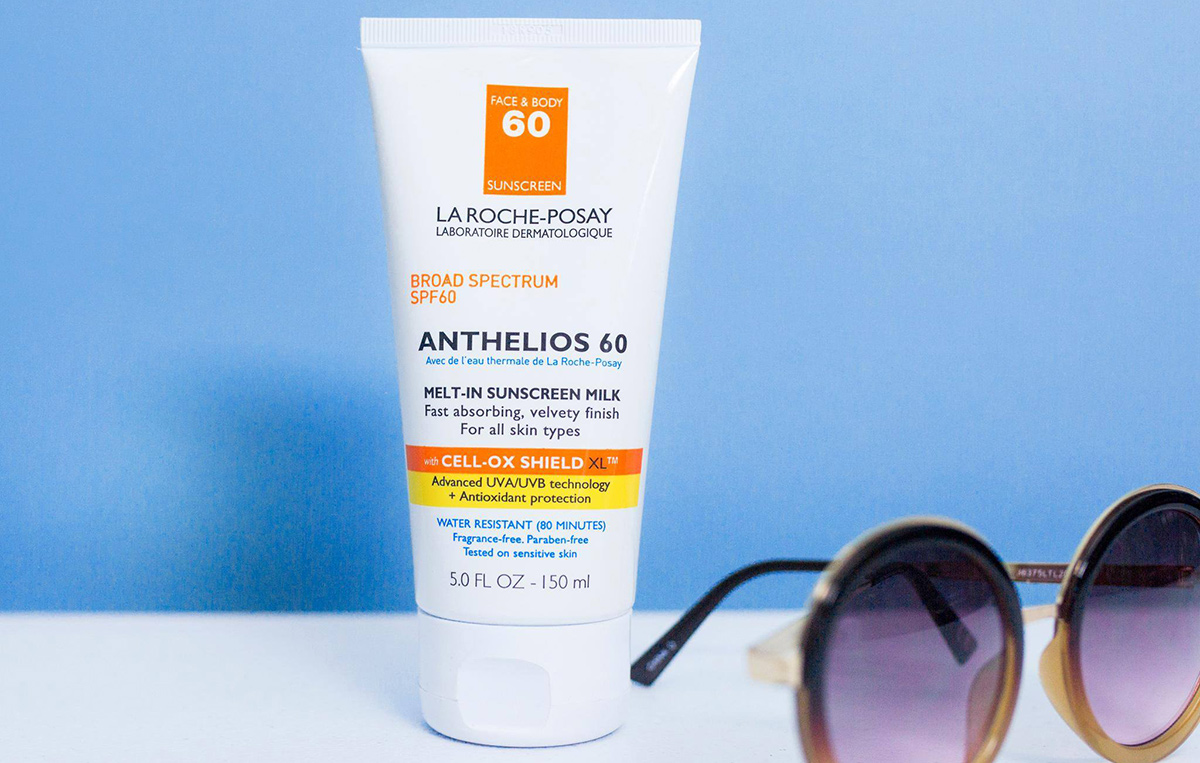 la roche posay anthelios sunscreen with blue background and sunglasses on table