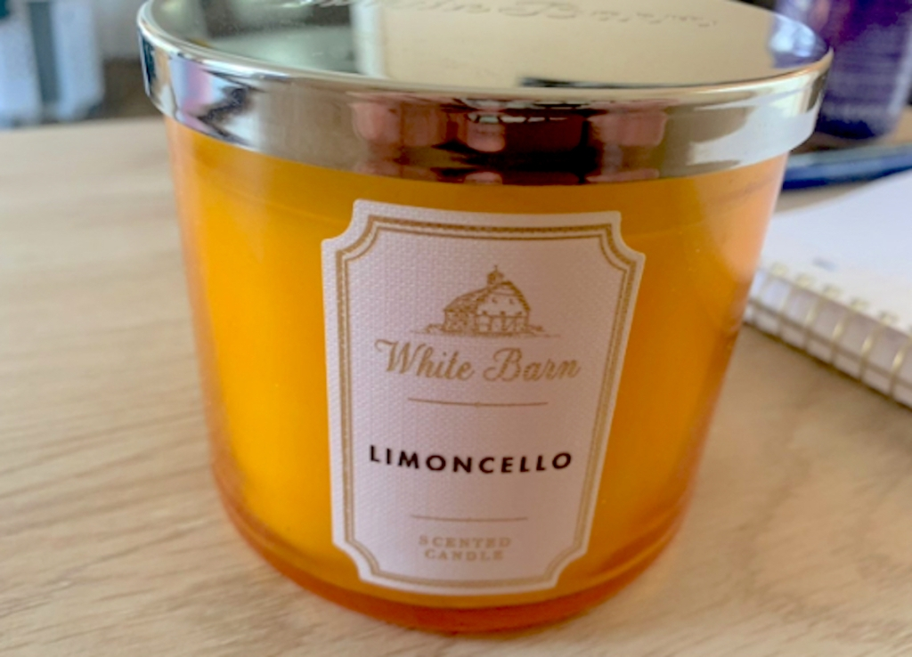orange limoncello candle with silver lid sitting on wood table