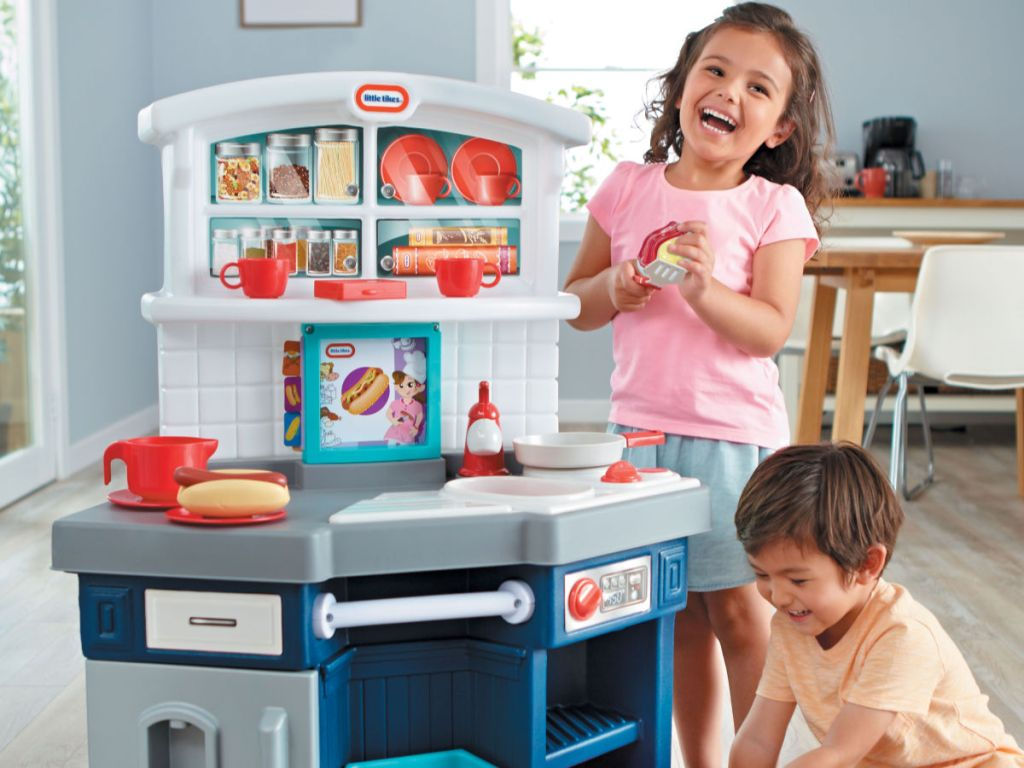boy and girl playing with little tikes kitchen set in house
