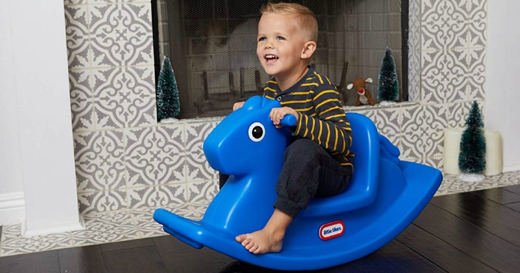 little boy on blue rocking horse in front of fireplace