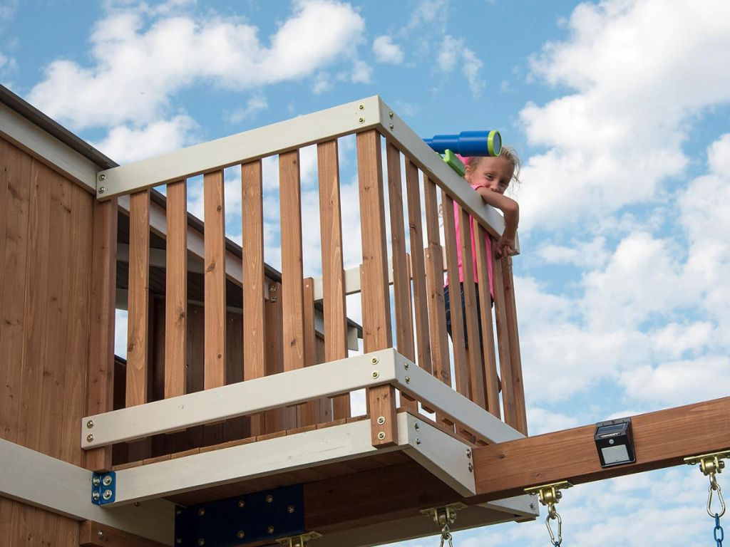 girl on lookout tower of play set with telescope