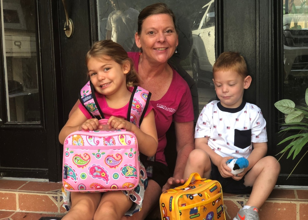 grandma with boy and girl with lunchboxes