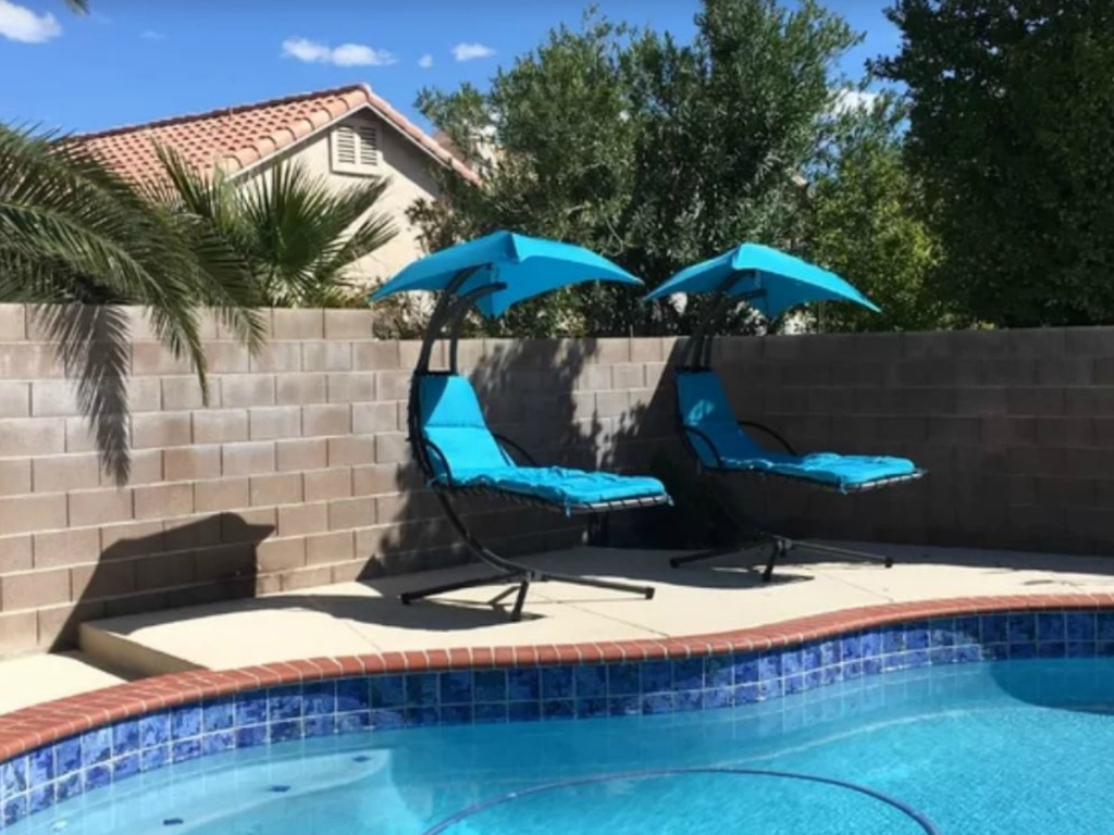 two blue chairs with sun shades next to a pool