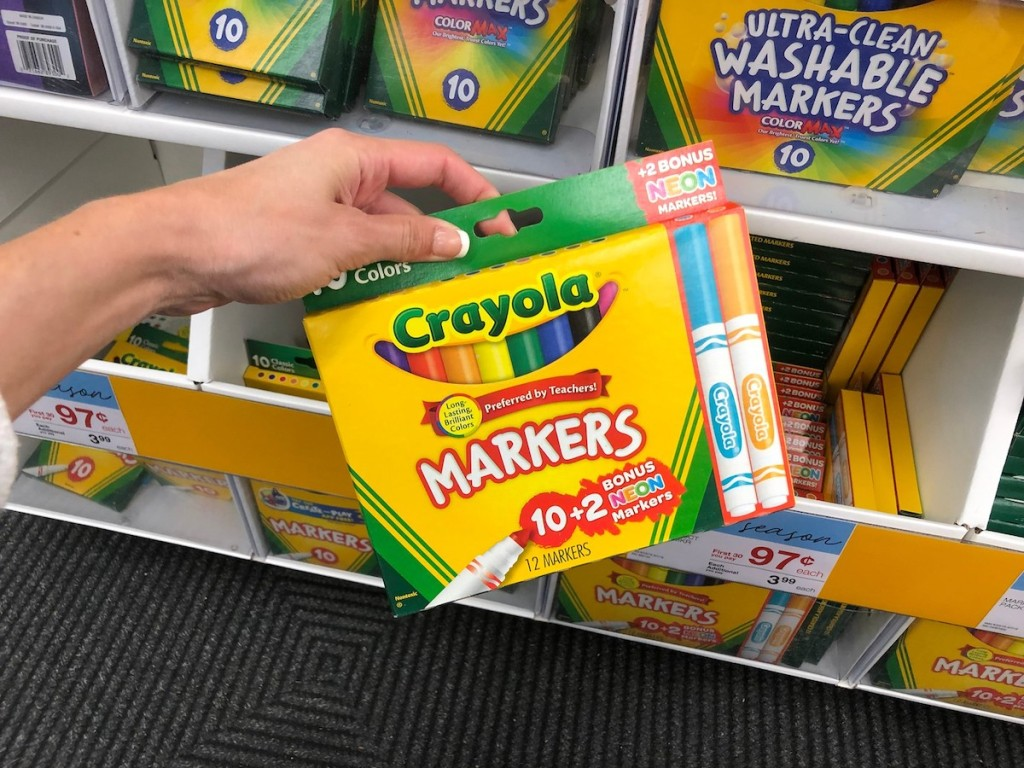 Hand holding a bonus pack of Crayola markers