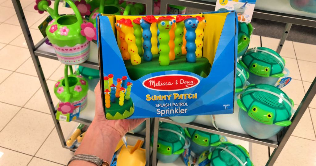 hand holiding melissa & doug sunny patch with more water toys in the background