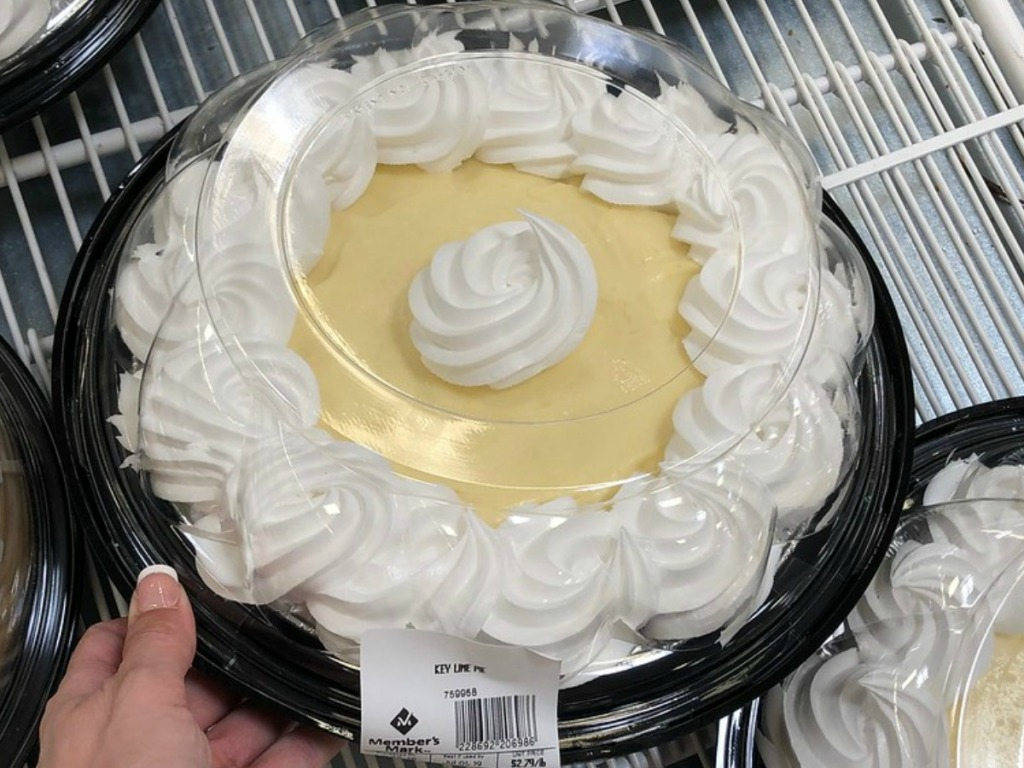 hand holding pie with whip cream