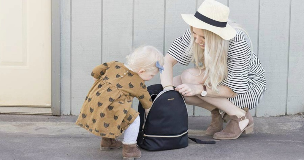 woman opening diaper bag backpack and baby looking through bag