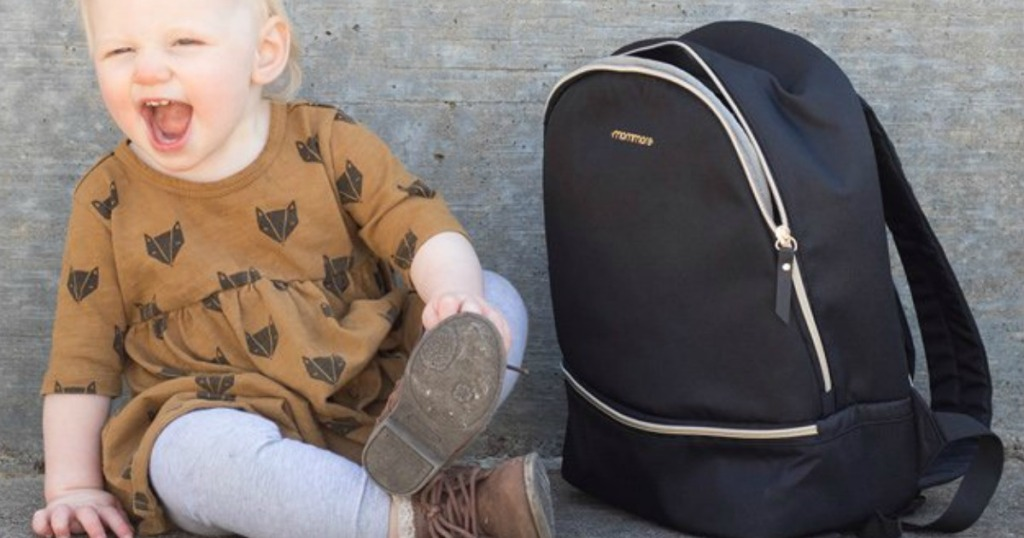 baby laughing while sitting with diaper bag backpack
