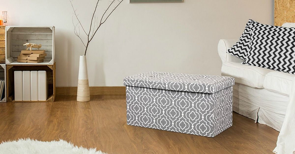 lift top ottoman bench in front of a couch, on a hardwood floor, with the top on