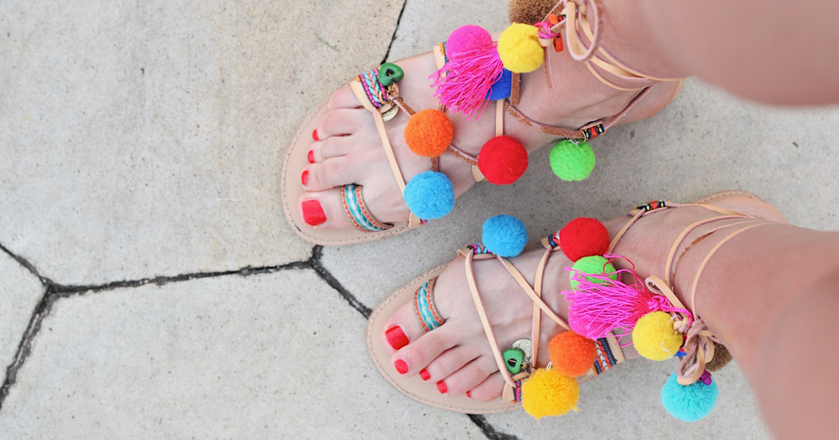 woman with red toenails wearing bright sandals