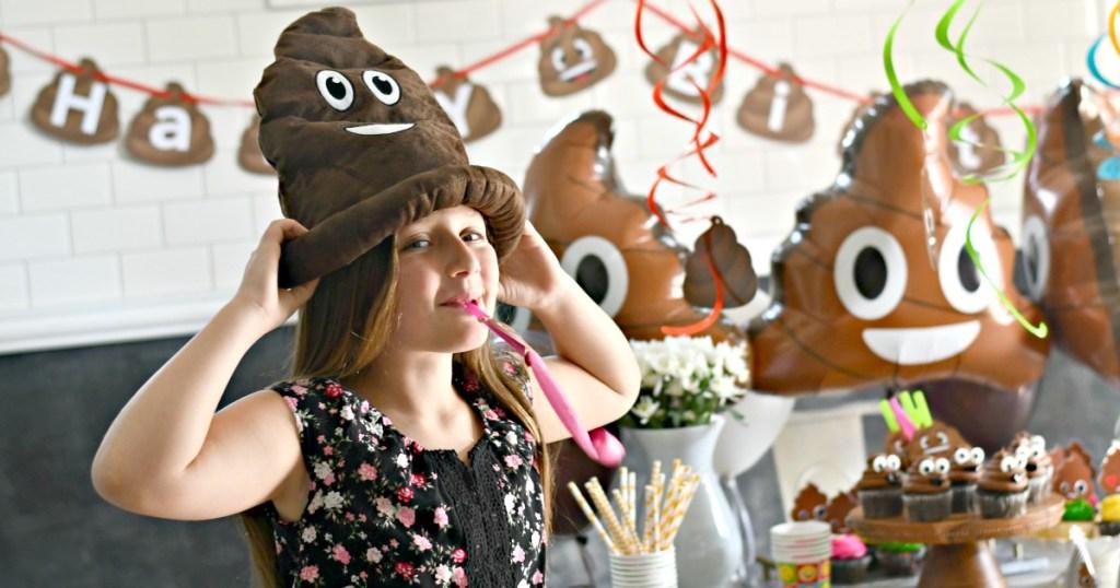 girl with poop emoji hat on at poop themed party