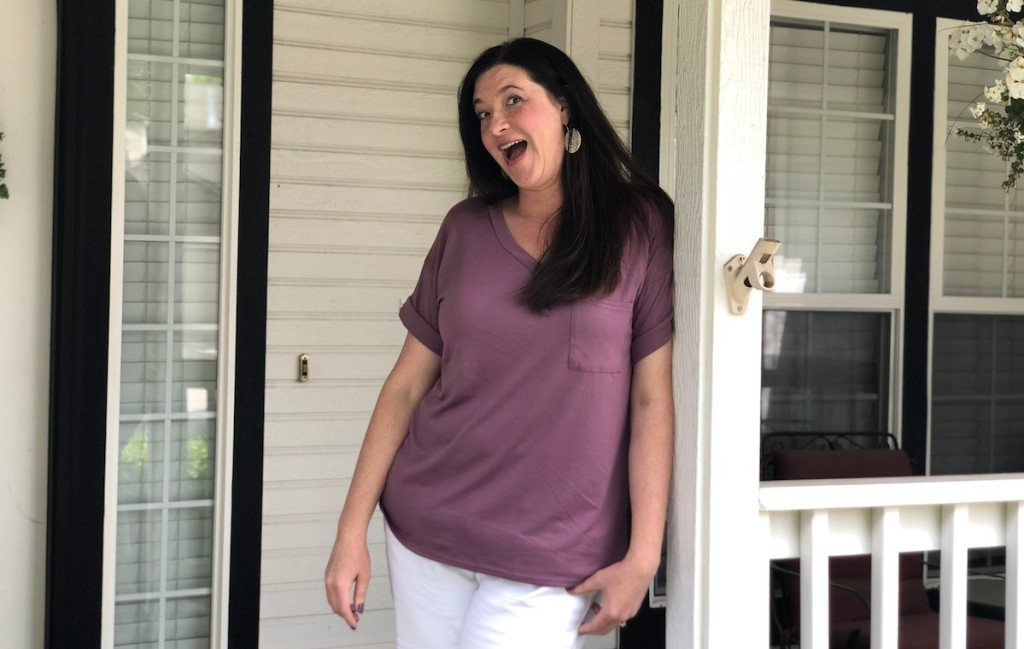 woman wearing purple short sleeve shirt and white pants standing outside on porch