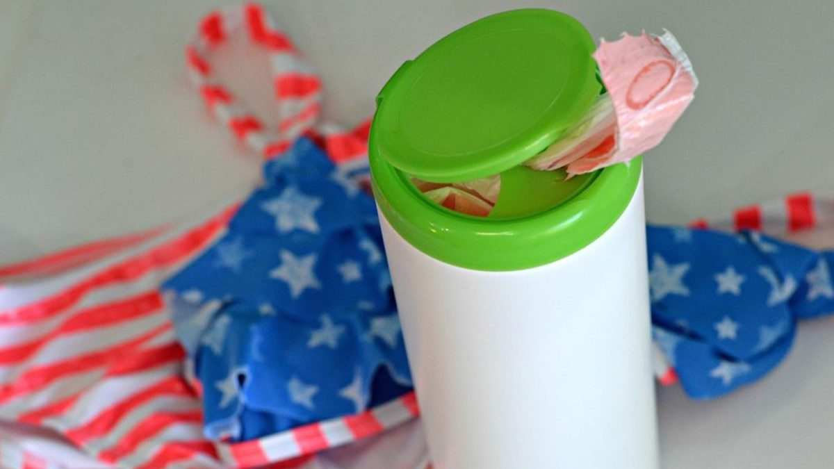 wipes container with trashbags inside and flag bathing suit in background