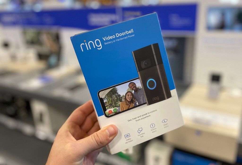 hand holding a ring doorbell in blue box in store