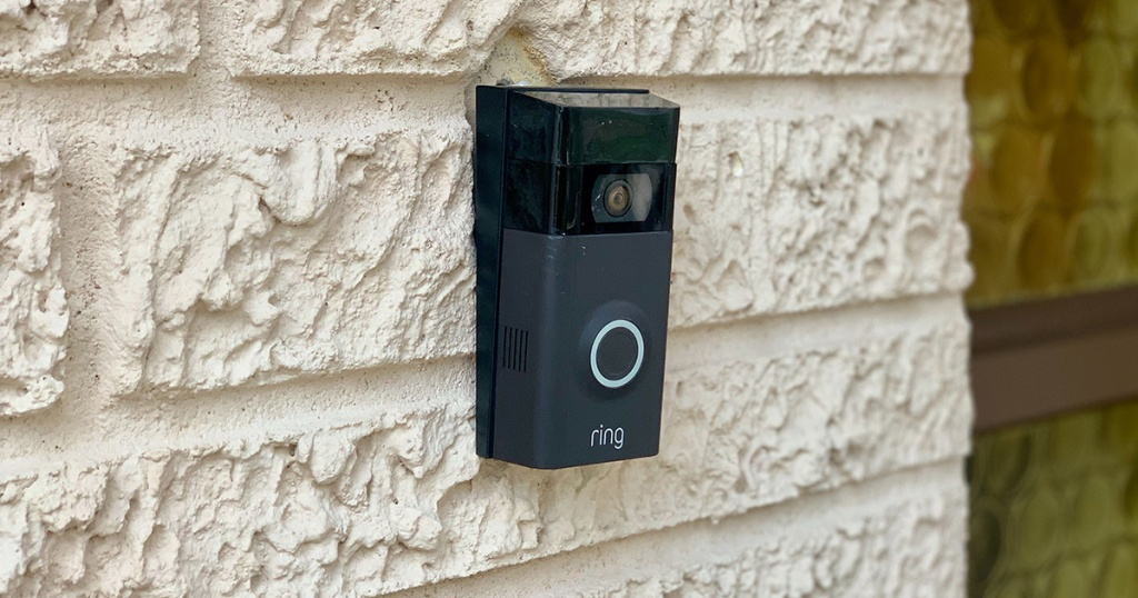 black ring doorbell on white brick house