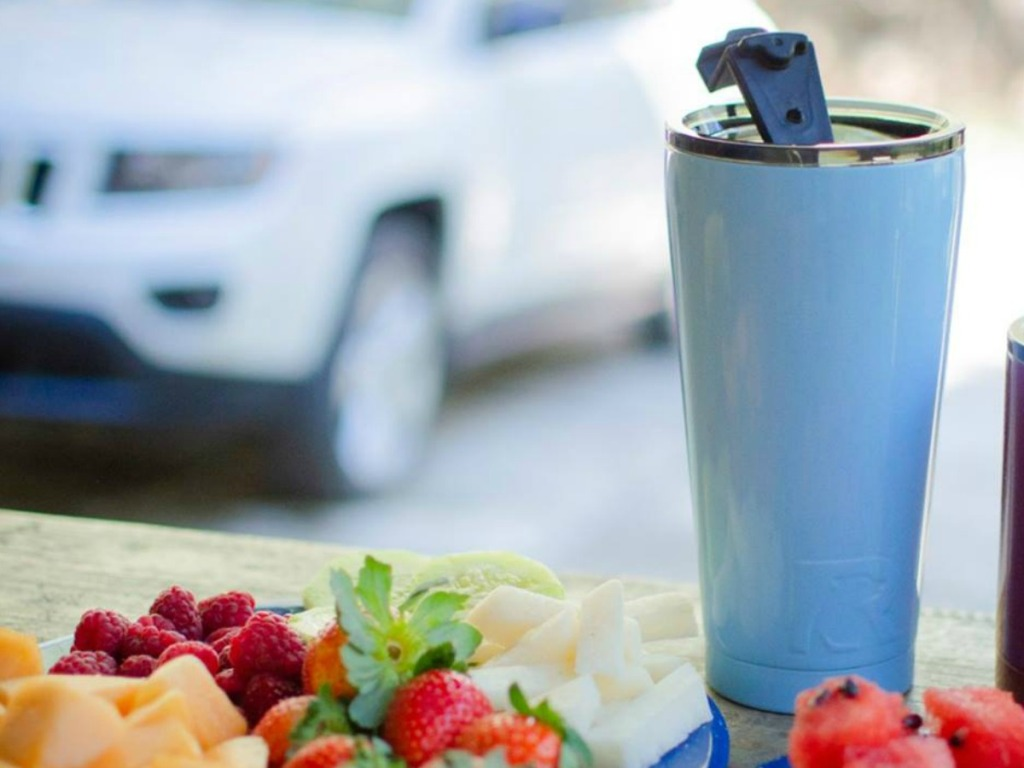 blue water bottle on table with strawberries and cheese