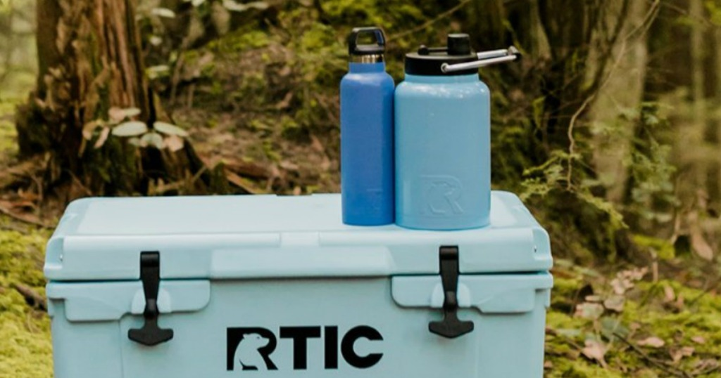cooler with blue water bottles on it in the woods
