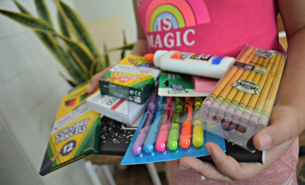 girl holding various school supplies writing utensils